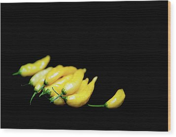 Yellow Chillies On A Black Background Wood Print