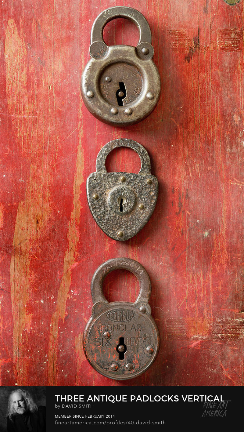 Three antique padlocks on a weathered red painted wood board. 