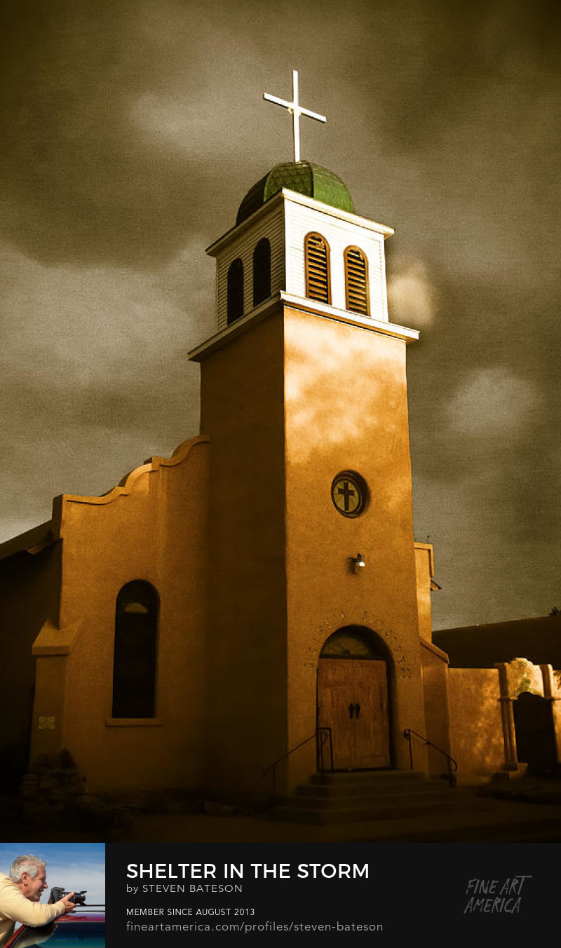 The steeple and cross of this adobe church in Cerrillos, New Mexico is illuminated by the evening sun in the middle of a dark ominous storm. The town of Cerrillos has been the location of several movies and television shows.