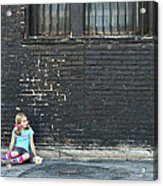 Girl Sitting On Ground Next To Brick Wall Acrylic Print
