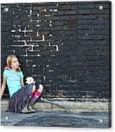 Girl Sitting On Ground Next To Brick Wall Acrylic Print