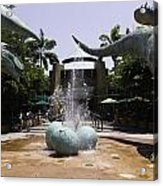 A Water Fountain With Dinosaur Eggs And Dinsosaurs In Universal Studios Acrylic Print