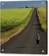 A Woman Running On A Dirt Road Acrylic Print