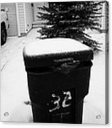 bag sticking out of litter waste bin covered in snow outside house in Saskatoon Saskatchewan Canada Acrylic Print