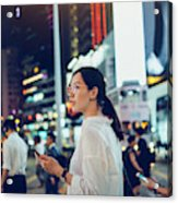 Beautiful Asian woman using mobile phone while crossing road in busy downtown city street at night Acrylic Print