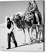 bedouin guide in modern clothing leads british tourists riding camels and wearing desert clothes into the sahara desert at Douz Tunisia Acrylic Print