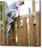 Boy Climbing Over Wooden Fence Acrylic Print
