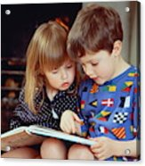 Boy(4-5)and girl(2-3)sat by fire in pyjamas reading book together Acrylic Print