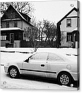 car covered in snow parked by the side of the street in front of residential homes caswell hill Sask Acrylic Print by Joe Fox