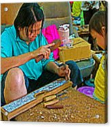 Child Watches As Mom Works In Teak Wood Carving Shop In Kanchanaburi-thailand Acrylic Print