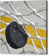 Close-up of an Ice Hockey puck hitting the back of the net as snow flies, front view Acrylic Print