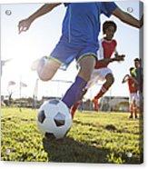 Close up of boy kicking soccer ball Acrylic Print