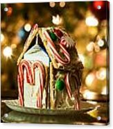Gingerbread House Against A Background Of Christmas Tree Lights Acrylic Print