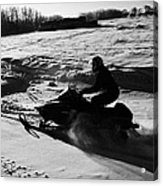 man on snowmobile crossing frozen fields in rural Forget Saskatchewan Acrylic Print by Joe Fox
