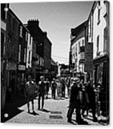 pedestrians walking down closed pedestrian area of quay street on sunny sunday afternoon Galway city Acrylic Print