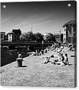 people enjoying the sunshine on the quay next to the corrib river on a sunday afternoon Galway city  Acrylic Print