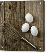 Three Eggs And Whisk Or Egg Beater On Rustic Wood Background Acrylic Print