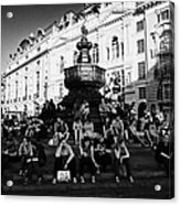 tourists and visitors sit on the steps of the eros statue in picadilly circus London England UK Acrylic Print