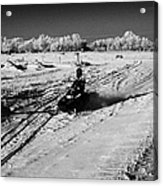 two men on snowmobiles crossing frozen fields in rural Forget Saskatchewan Canada Acrylic Print