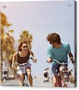 Woman chasing man while riding bicycle Acrylic Print