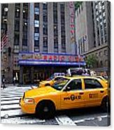 Yellow Cabs Pass In Front Of Radio City Music Hall Acrylic Print