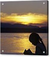 Young Girl Silhouetted Reading A Book On The Beach At Sunset Acrylic Print