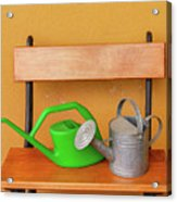 A Watering Can Of  Aluminium And A Plastic One Laid On Wooden Bench Acrylic Print