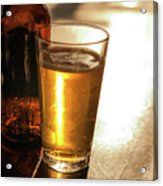 Backlit Glass Of Beer And Empty Bottle On Table Acrylic Print