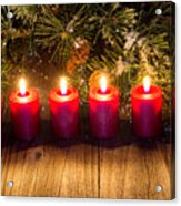 Glowing Red Candles With Snow Covered Evergreen Branch On Rustic Acrylic Print