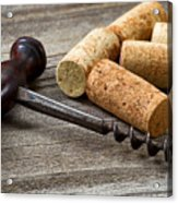 Old Corkscrew With Used Corks In Background On Aged Wood Acrylic Print