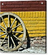 Old Wooden Wheel Against A Wall Acrylic Print