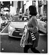 woman crossing crosswalk in front of yellow cabs in the evening in Times Square New York City USA Acrylic Print
