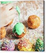 Woman's Hand Coating A Donut With Green Frosting. Acrylic Print