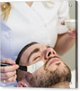 Young man receiving a facial treatment in beauty spa. Acrylic Print