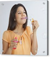 Young woman blowing soap bubbles Acrylic Print