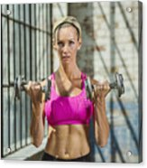 Caucasian woman lifting weights in warehouse Acrylic Print