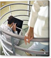 Focus on man sitting on stairs with cell phone and laptop computer, person walking up stairs in foreground, blurred. Acrylic Print