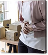 Healthcare medical concept: the young lady have a stomachache or menstruation pain during work in the office. Acrylic Print