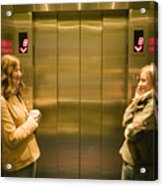 Two young women waiting in elevator Acrylic Print
