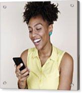 Woman smiling using phone Acrylic Print
