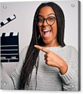 Young african american director girl filming a movie using clapboard over isolated background very happy pointing with hand and finger Acrylic Print