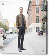 Young man standing on city sidewalk Acrylic Print
