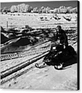 man on snowmobile crossing frozen fields in rural Forget Saskatchewan Canada Canvas Print