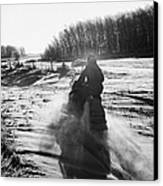 man on snowmobile crossing frozen fields in rural Forget Saskatchewan Canada Canvas Print by Joe Fox