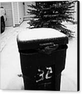 bag sticking out of litter waste bin covered in snow outside house in Saskatoon Saskatchewan Canada Canvas Print