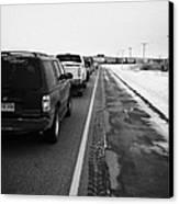 cars waiting on train crossing trans-canada highway in winter outside Yorkton Saskatchewan Canada Canvas Print by Joe Fox