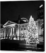 christmas tree and german flag flying fluttering on flagpole outside reichstag building Berlin Germany Canvas Print