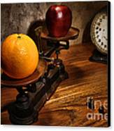 Comparing Apple And Orange Canvas Print by Olivier Le Queinec