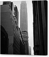 empire state building shrouded in mist in amongst dark cold buildings on 33rd Street new york city Canvas Print by Joe Fox