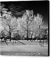 empty childrens playground with hoar frost covered trees on street in small rural village of Forget  Canvas Print
